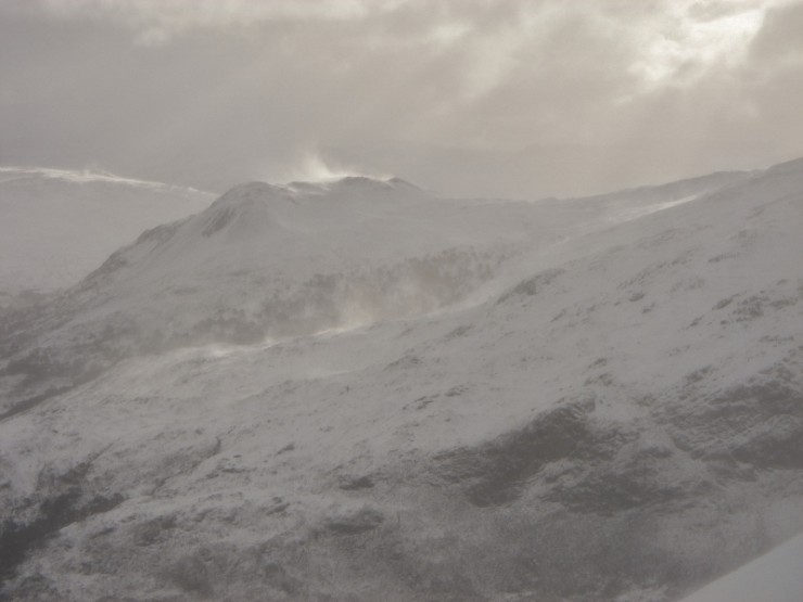 Spindrift rising off exposed ridges and summits.